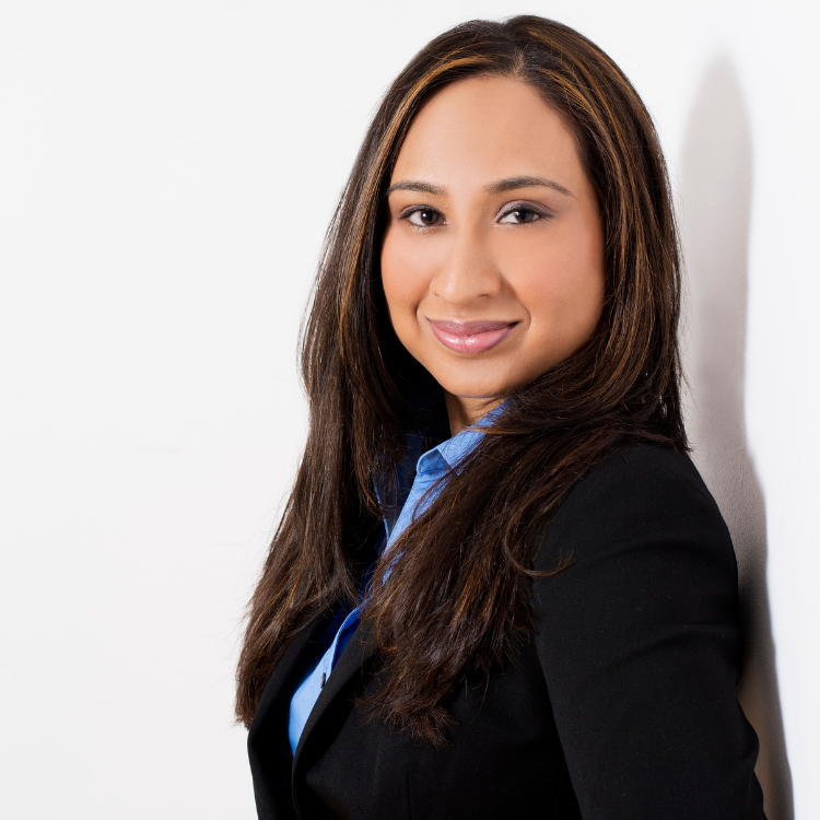 Image of Fazeena Haniff in a black suit and blue shirt leaning against a wall